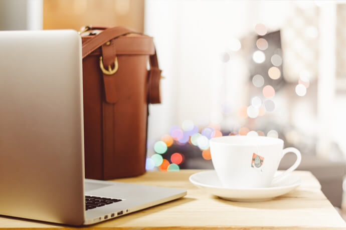 a desk with a computer, cup of tea, and bag