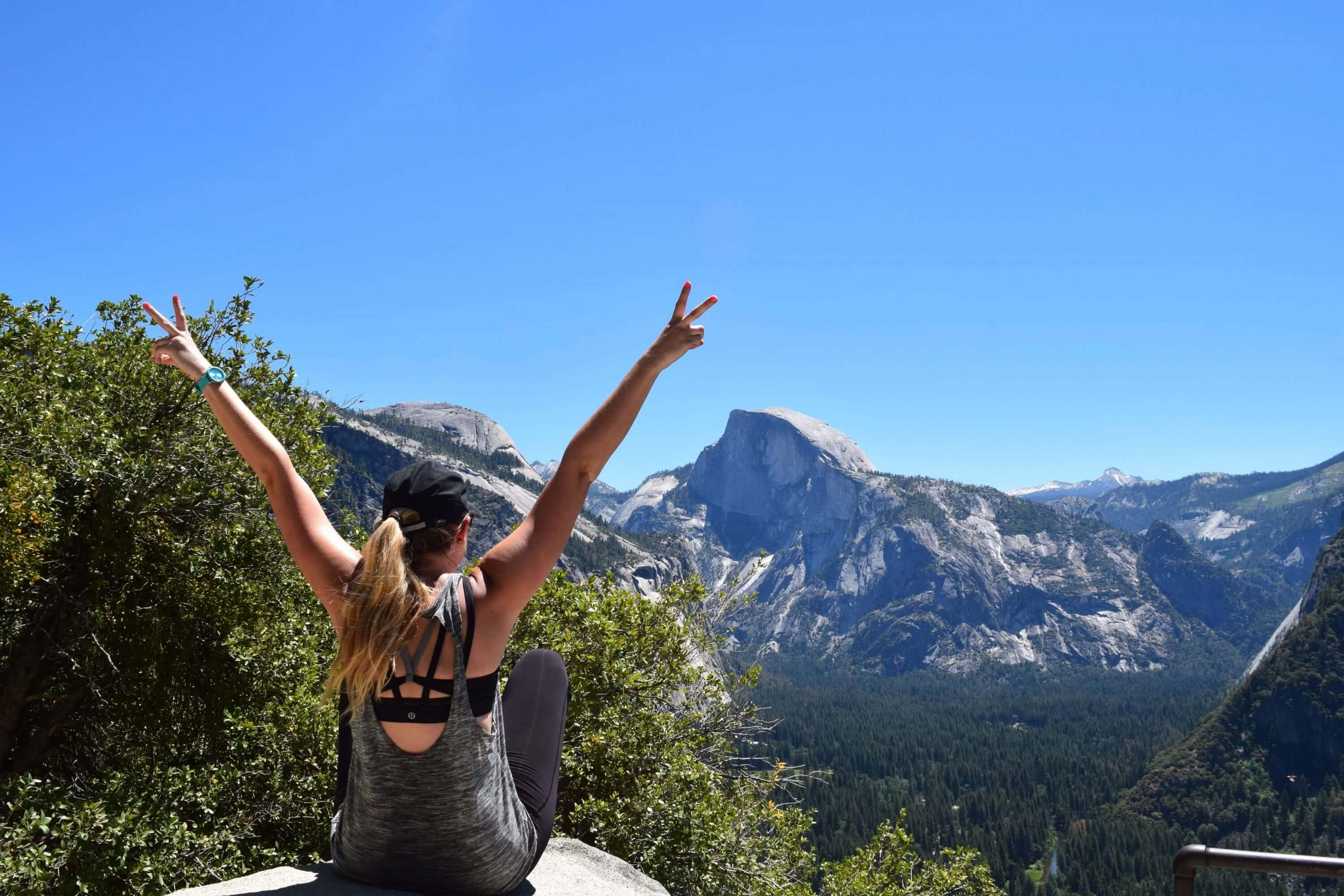 woman sitting on the edge of a mountain in Yosemite