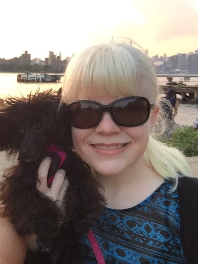 a woman holding a poodle