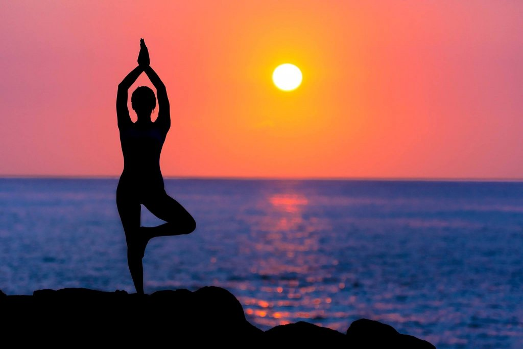 a women doing yoga at sunset