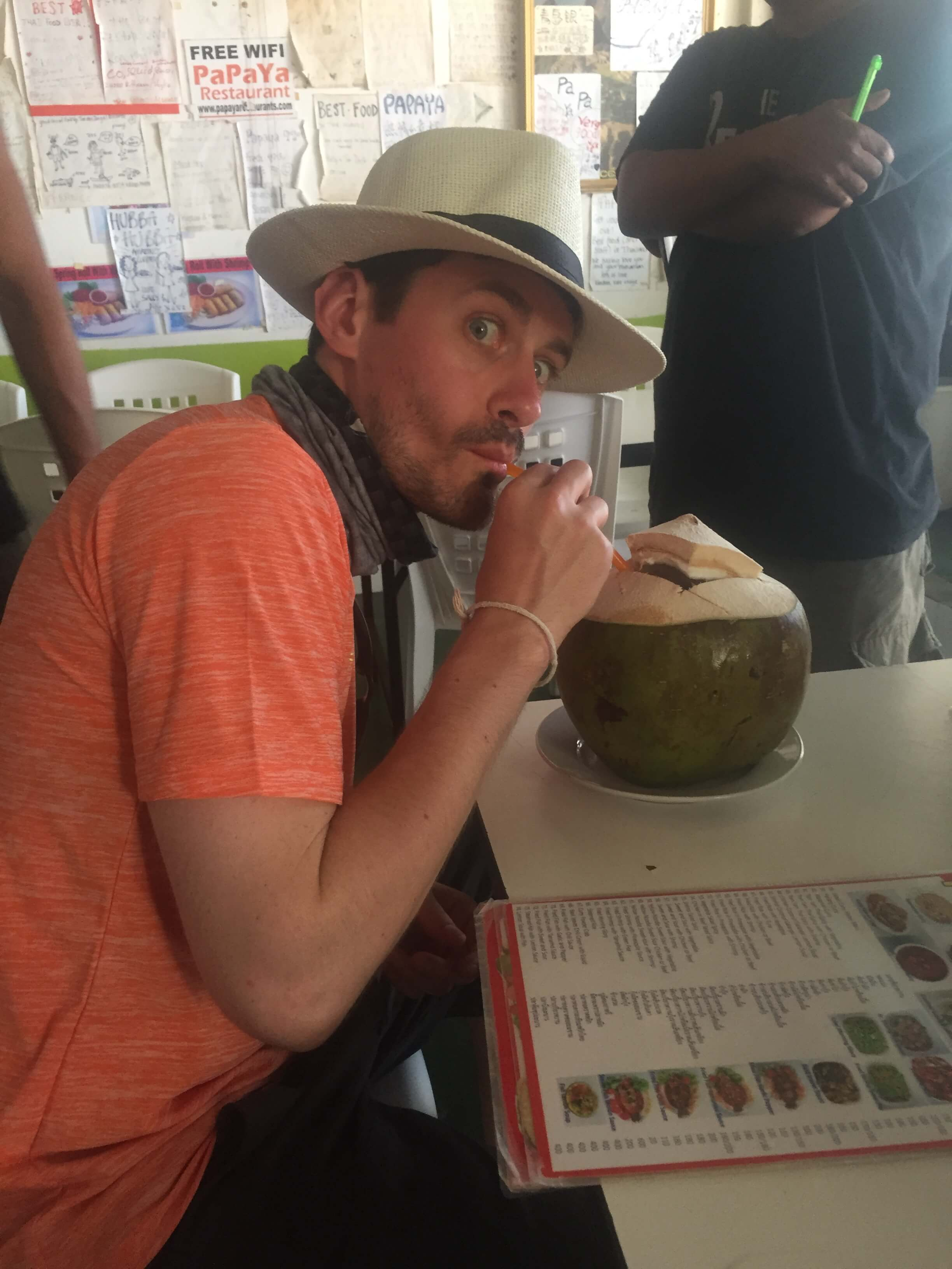 a man drinking a coconut