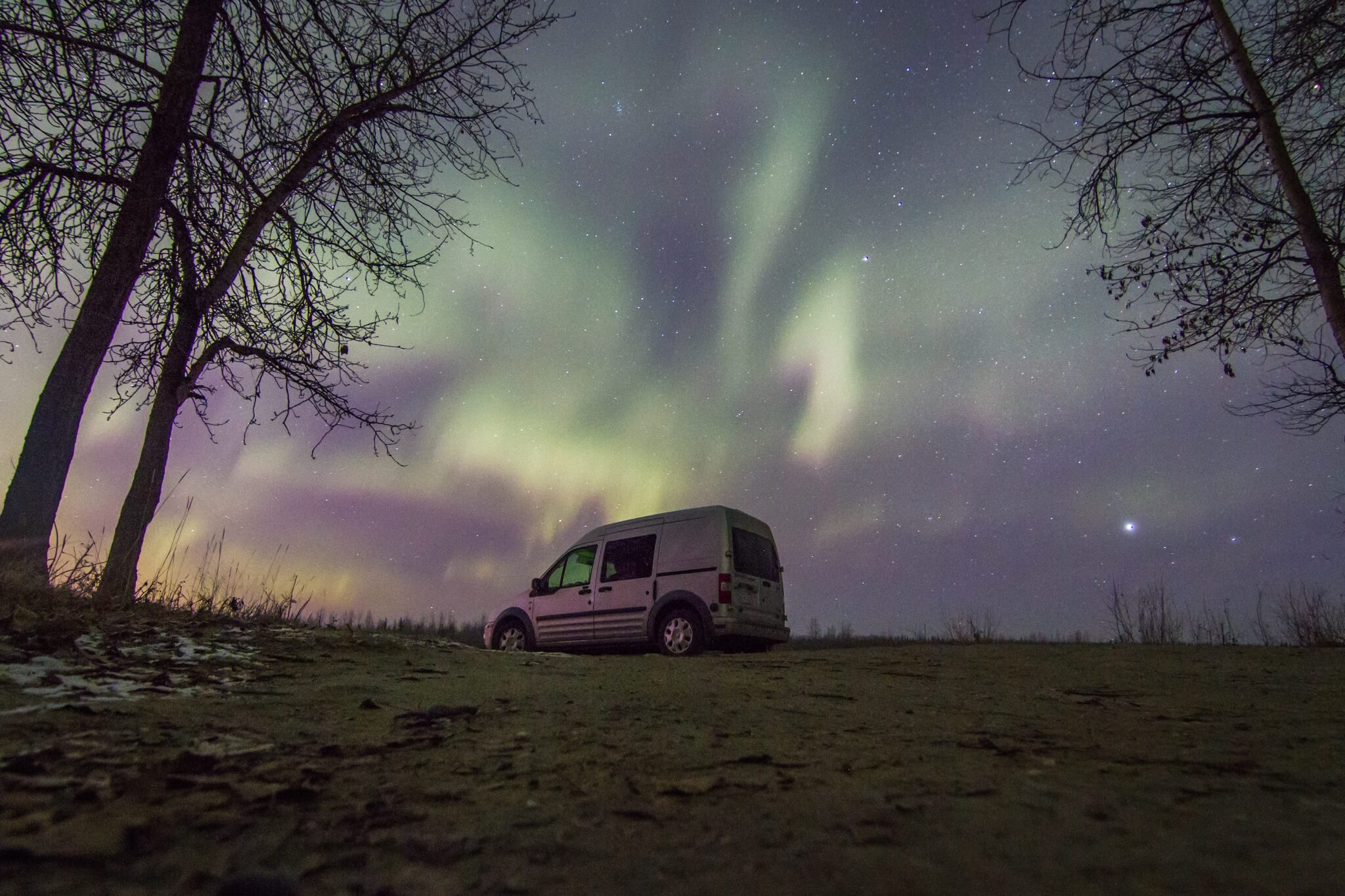 a van with the northern lights in the sky