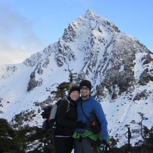 a man and woman standing next to a mountain