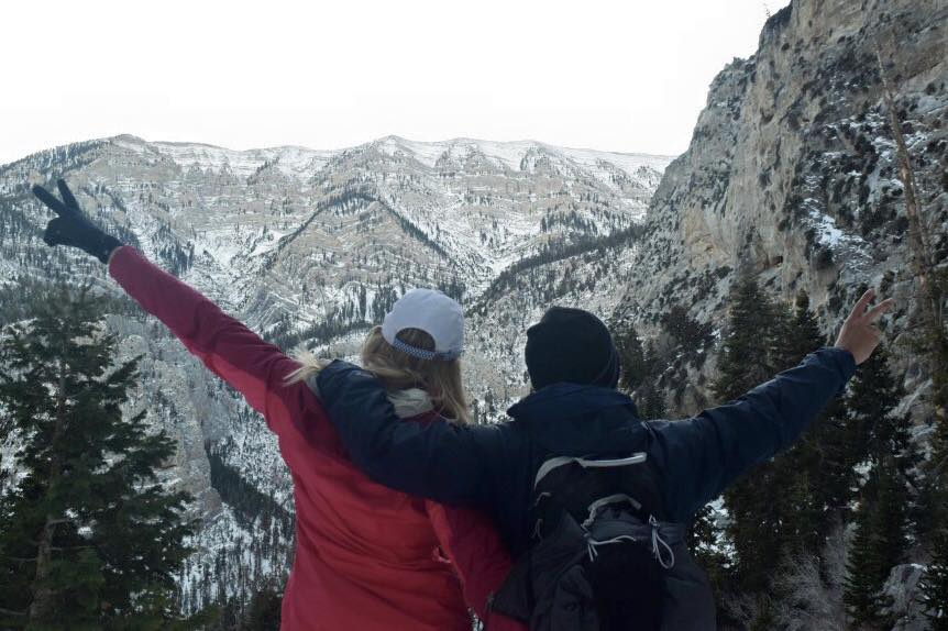 2 people at the top of a snow topped mountain