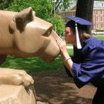 women in a graduation cap, kissing the penn state nittany lion statue.
