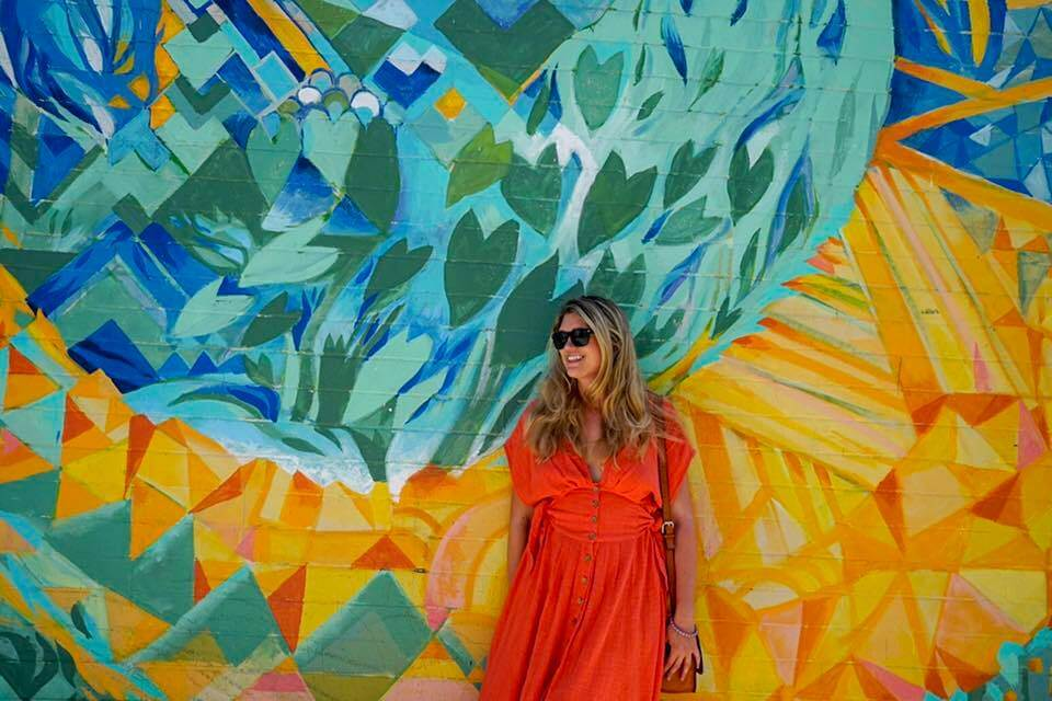 a women standing in front of a mural