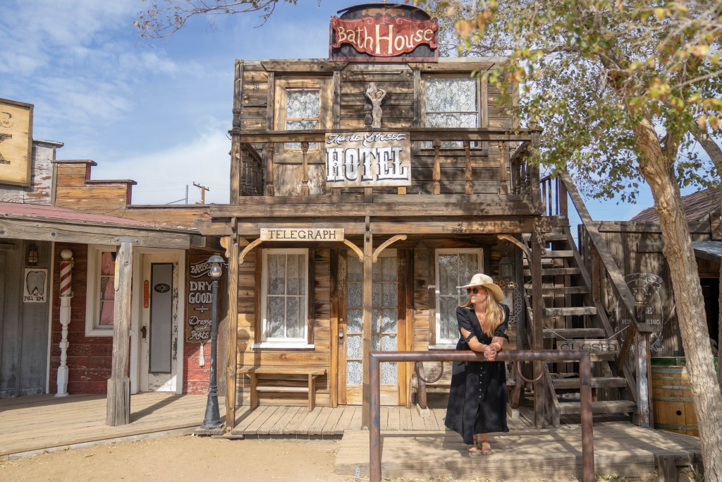 a women standing in front of an old west style hotel