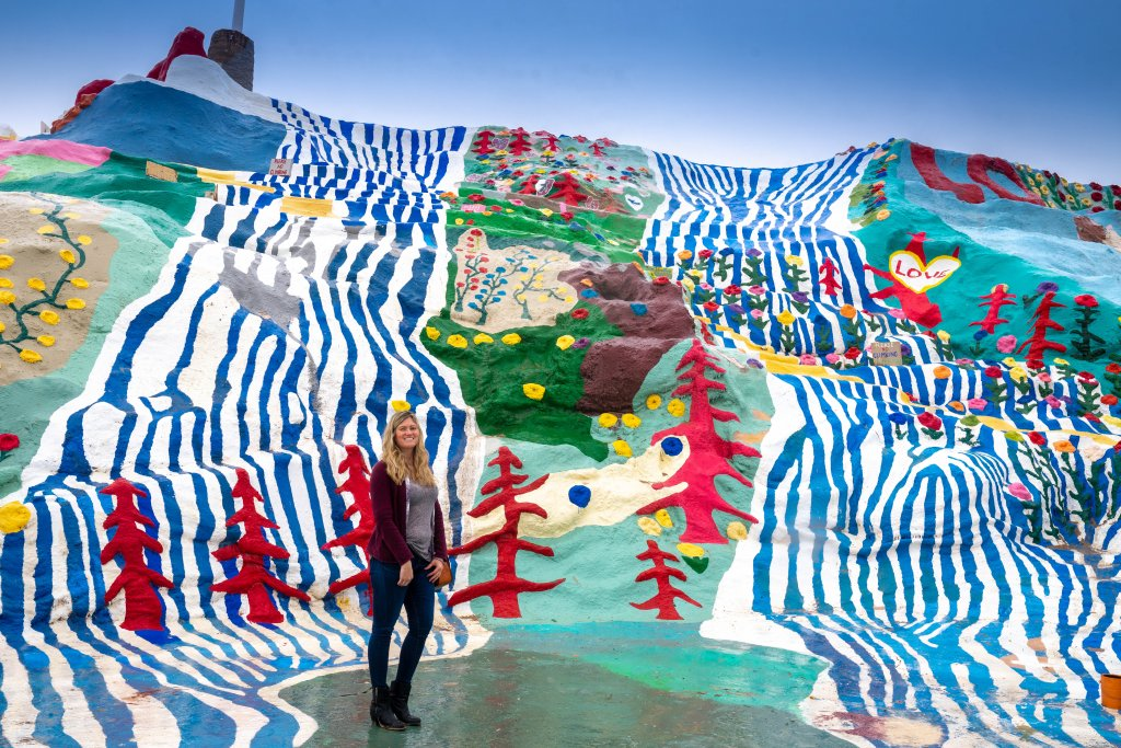a women standing in front of an art installation at salvation mountain