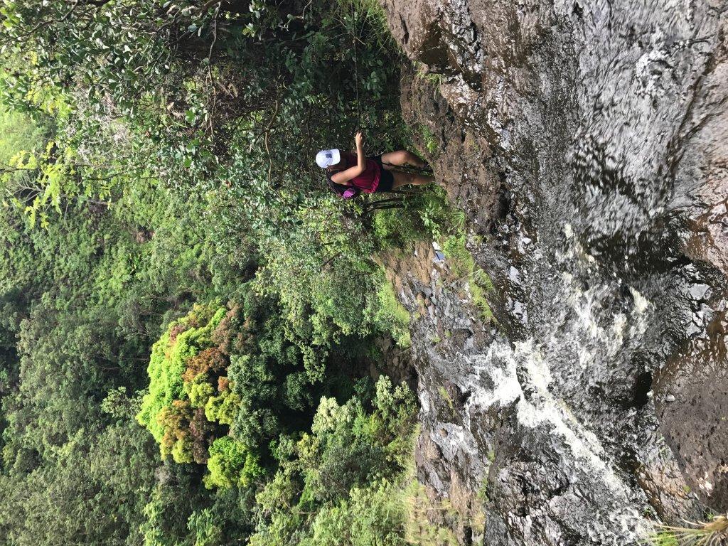 a women climbing up a waterfall