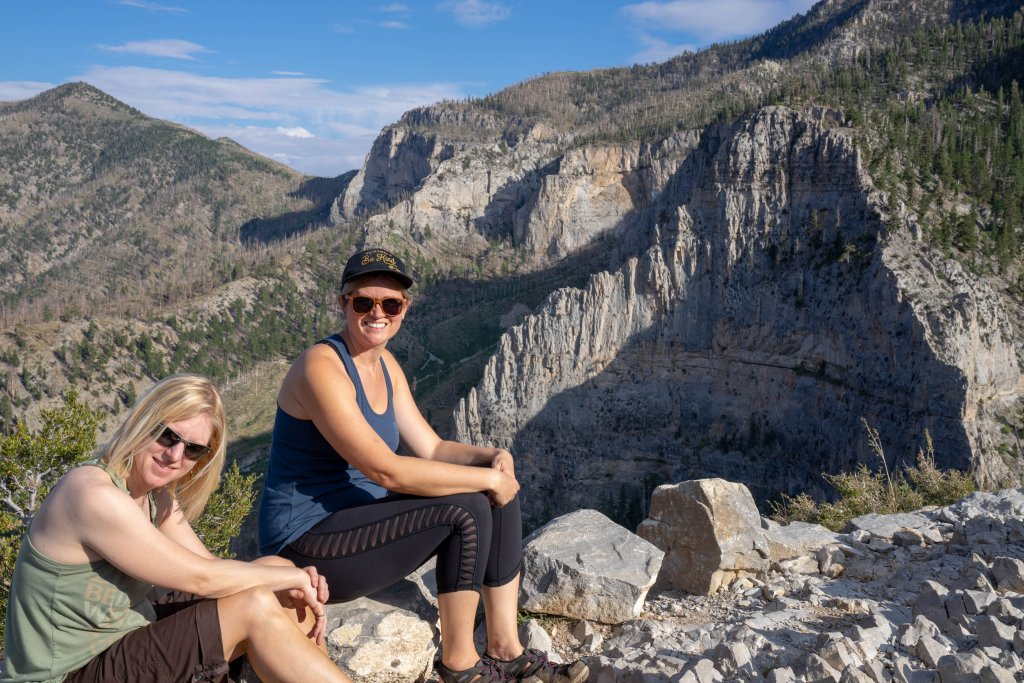2 women sitting with cathedral rock in the background