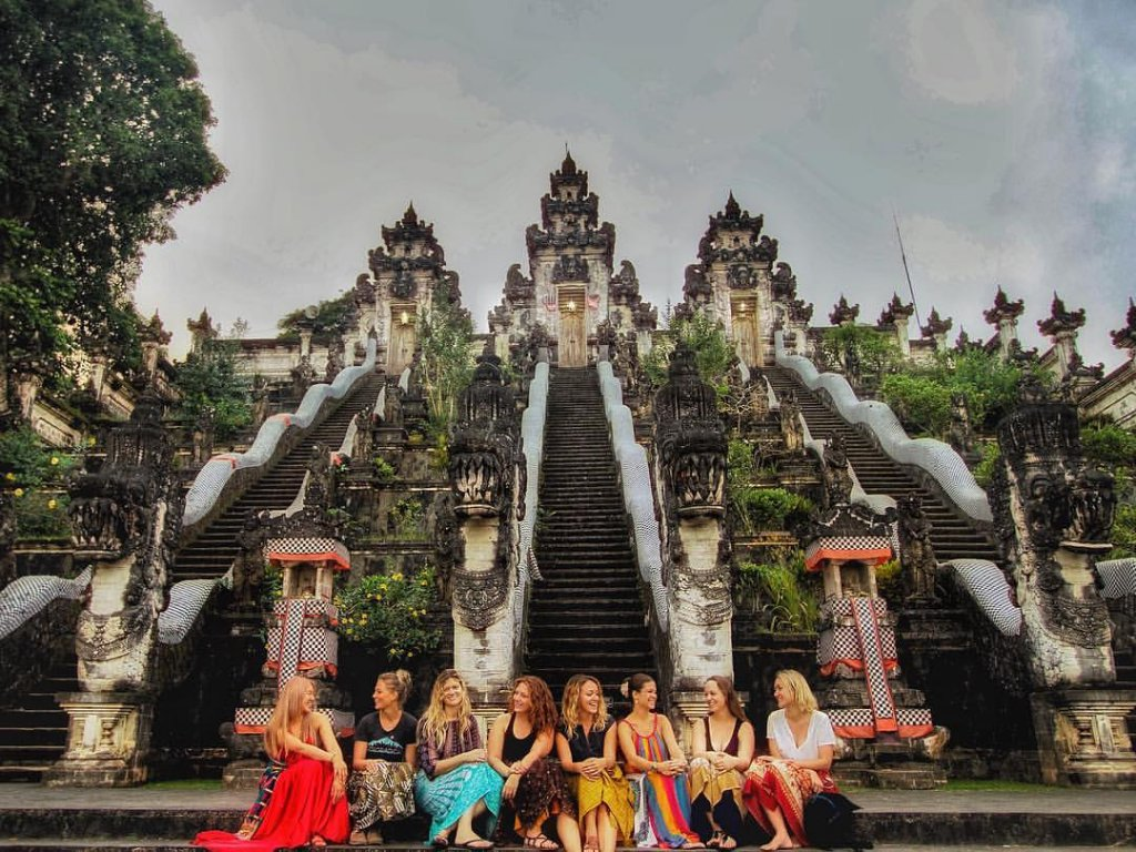 women sitting on the stairs of a temple in Bali