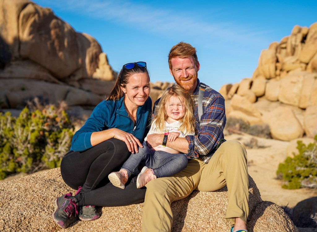 a travel therapist family sitting on a rock