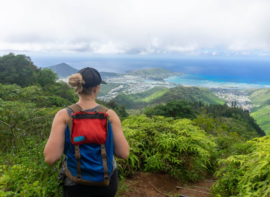 a women standing on the top of a mountain looking at views of a valley and ocean