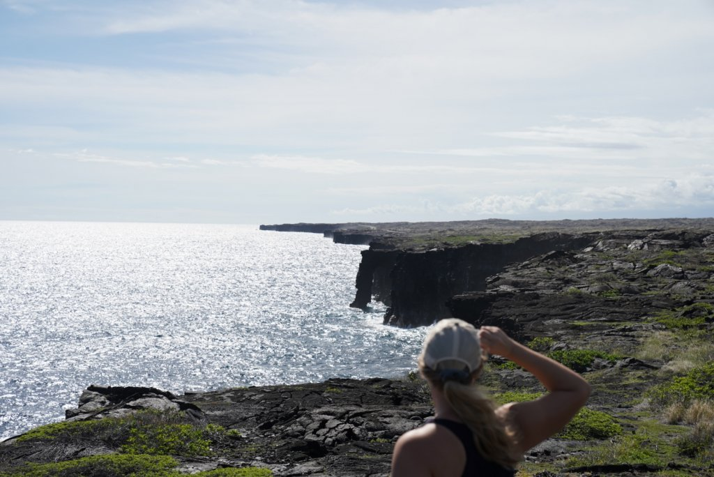 a women looking at the sea arch on chain of craters road