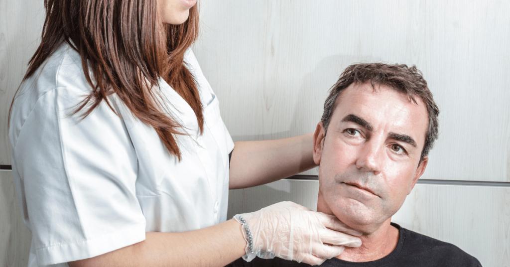 a women feeling a mans neck while he swallows