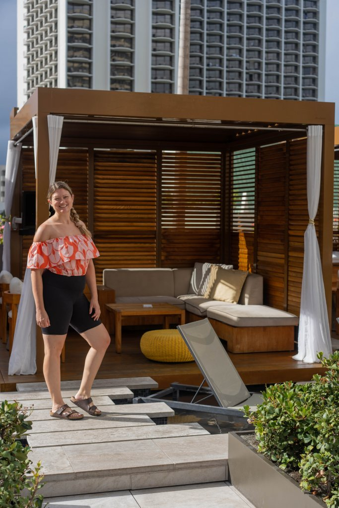 a women standing next to a pool cabana
